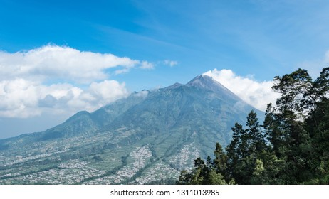 The very active volcano peak of Mount Merapi in Java Indonesia on a clear day with blue sky.