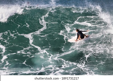 Very active young girl seen surfing a turbulent ocaen from above and distant.