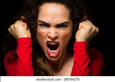 A very angry aggressive woman is clenching her fists in rage