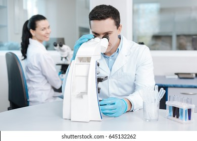 Very attentive lab assistant looking into microscope