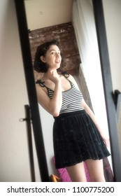 Very attractive woman with dark hair and tanned skin looking at the camera. She is wearing a black and white striped top, and standing in front of an antique mirror.