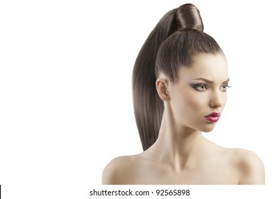 very attractive young brunette with long hair and tail and creative hair style looking proud, she is turned of three quarters and looks down at left