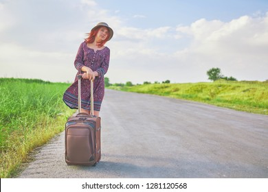 Very awesome female traveler in summer dress and hat hitchhiking with suitcase on the road at spring. Pretty woman stands next to the baggage waiting for the transport. Tourist concept