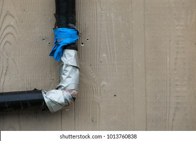 Very bad plumbing job done on a pipe on the outside of a house closeup