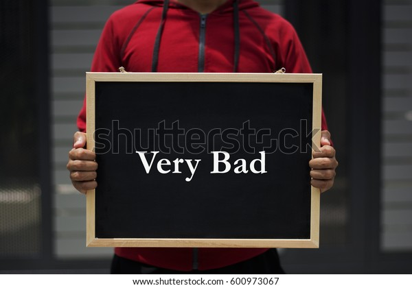 very bad written on blackboard with someone is holding it