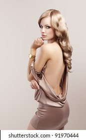very beautiful and attractive young blond woman in elegant silk dress and with old fashion hair style and golden clock on wrist