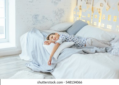 Very beautiful blonde boy in blue shirt in a small flowered barefoot on the bed and dreaming
