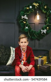 Very beautiful blonde cheerful boy sitting in a sofa in the hallway light on the background of the Christmas tree with toys from waiting for the New Year and Christmas