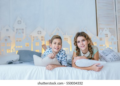 Very beautiful blonde young girl with pigtails and a boy in a blue shirt in a small flowered barefoot lie on the bed and pulls his legs, playing with pillow, smiling, laughing