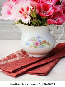 Very beautiful bouquet of pink flowers in a porcelain pincher decorated with floral pattern on shabby wooden background with linen napkin. Concept for greeting card. Bright white color