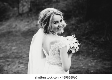 very beautiful bride in a white dress standing outdoors