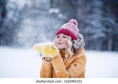 Very beautiful bright young girl in a red hat and yellow mittens on the background of a winter park in the snow. Winter holidays concept. Throw and blow snow