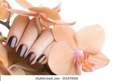 Very beautiful brown nails close up and flower.