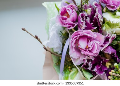 Very beautiful colorful blossoming flower bouquet of fresh Quicksand roses, carnations, ranunculus, peony, branches with buds,first leaves on white background.Flowers for special occasion,event.Happy