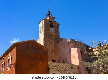 Very beautiful and colorful houses, and a church in the small French village of Roussillon, famous for its ochre rocks. France, Provence, Luberon.