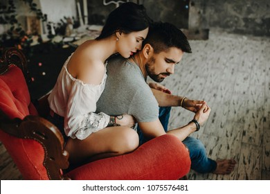 Very beautiful couple sitting on vintage red chair, where tattooed with red lips girl is embracing from back his lover waiting to kiss his neck while he is turning his head to her gently.