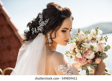 Very beautiful, dark-haired bride with ornaments in her hair, with earrings with precious stones and lush white lace dress on your wedding day.