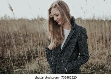 Very beautiful and fashion girl dressed in wool coat posing at camera on bulrush background on cold weather. Young woman smiling and looking down. Autumn. Outdoor.
