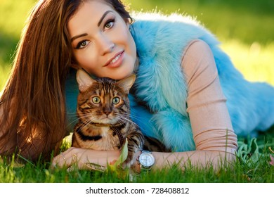 A very beautiful fashionable girl with a brown-haired woman lies on the grass and holds a Bengal cat, in a green park