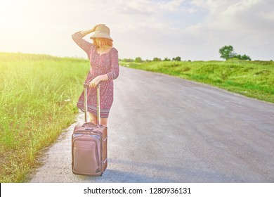 Very beautiful female tourist  in summer dress and hat hitchhiking with suitcase on the road at spring. Woman stands next to the Luggage waiting for the transport. Travel concept