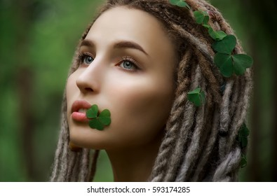 Very beautiful girl with a clover in her lips. Beauty, nature and  st Patrick concept