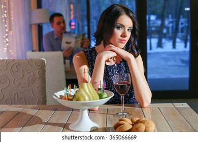 Very beautiful glamour girl in a dark blue dress sits at restaurant at a table