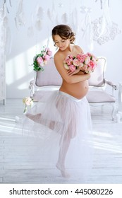 very  beautiful pregnant woman with a big bouquet of flowers in a gentle interior