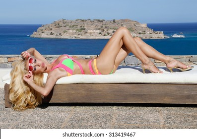 Very beautiful sexy blonde long-haired woman being in the sexy pink green orange color full swimsuit on the deckchair on the beautiful swimming pool in santorini and greece and spinalonga