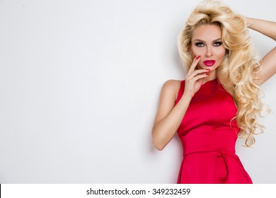 Very beautiful sexy blond-haired woman girl in a sexy short red dress crystals with long legs standing on a white background holding hands above his head