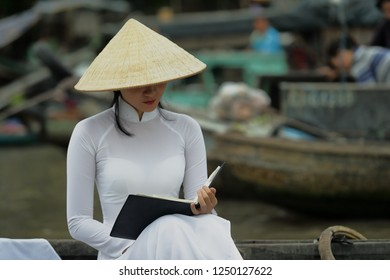 Very beautiful Vietnamese young woman in Mekong Delta.She dresses traditional Vietnamese clothes and sits on the boat  on the river.