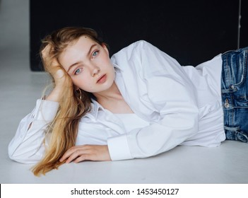 Very beautiful woman, wearing in white shirt, on the floor