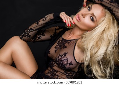 Very beautiful young blond sexy female model in erotic lingerie lace blouse in a cute makeup and sensory mouth on a black background