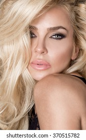 Very beautiful young blond sexy female model in cute makeup and sensory mouth, portrait, volume long blonde hair, amazing green eyes and big sensual lips