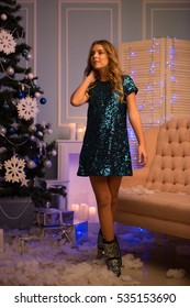 Very beautiful young blonde woman in a short shiny dress with long legs standing near the Christmas tree in the living room by the fireplace with candles in anticipation of Christmas and New Year.