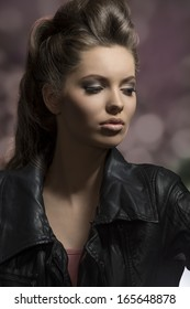 very beautiful young brunette female posing in dark fashion shoot with creative hair-style and modern leather jacket