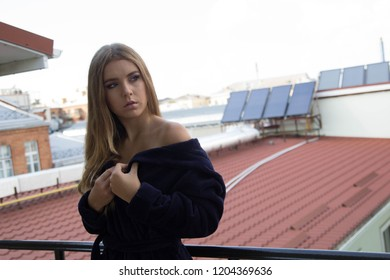 Very beautiful young girl with blond hair in a long blue robe stands on the roof of an old house