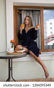 Very beautiful young girl with blond hair in a long blue robe sits in front of a glass table in the window on the roof of an old house and has a croissant with coffee and fruit