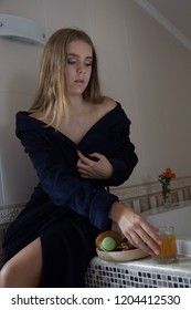 Very beautiful young girl with blond hair in a long blue robe sits in a round bath and has a croissant with coffee and fruit