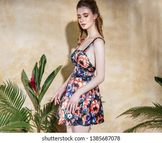 Very beautiful young girl with blond hair in a colored sundress dress is cute near the wall in the summer