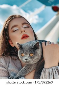 Very beautiful young girl with blond long hair in a gray mini dress with a big gray cat near the plane