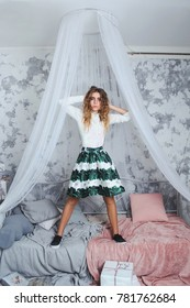 Very beautiful young girl in a green skirt is standing on the bed