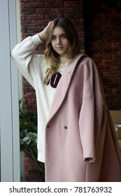 Very beautiful young girl in a pink coat