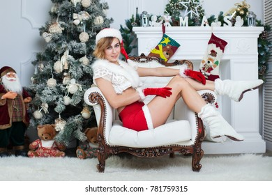 Very beautiful young girl sitting near the Christmas tree