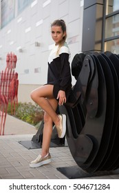 Very beautiful young girl the teenager in black fashionable dress with long legs standing near the supermarket. Summer.