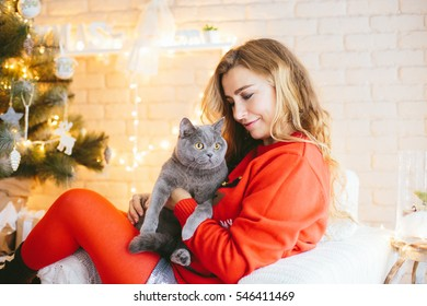 Very beautiful young mother in a red sweater and red socks with a cat sitting on their hands in anticipation of the New Year. Family happiness ...