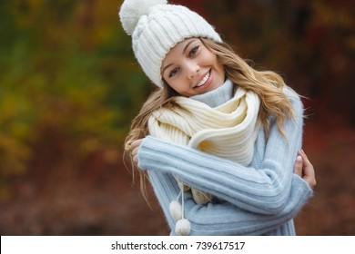 Very beautiful young woman on the autumn background. Close up portrait of smiling young pretty girl in the fall time.