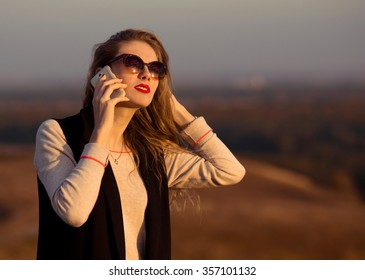 Very beautiful,awesome,beloved,super,pretty,divinely beautiful,with new,original,fine,beautiful sunglasses,red lips speaks by phone,discusses,communicates,expresses opinion,gives advice at sunset,nice