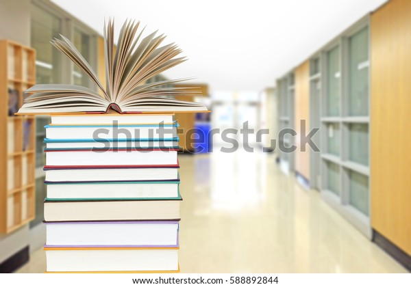 very blurry hall way as background with books in the front for education concept