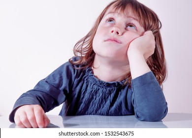 Very bored little cute baby girl looking tired and sick. Negative emotions, gestures, body language concept.