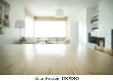 Very bright abstract living room design. Only the texture of the table in the front is in focus. The abundance of light turns the house into a lovely and cozy home. White walls with nice wood details.